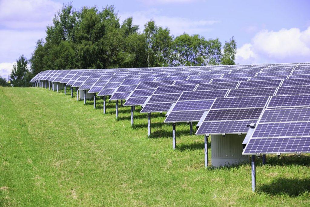modern solar panels in a beautiful green field