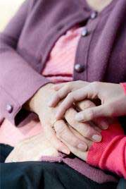 An elderly hand and a younger persons hand holding each other
