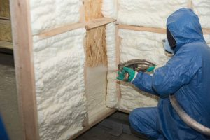 Workers spraying Foam Insulation into a wooden cell.