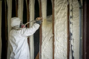 An image of a worker filling a closed cell with spray foam
